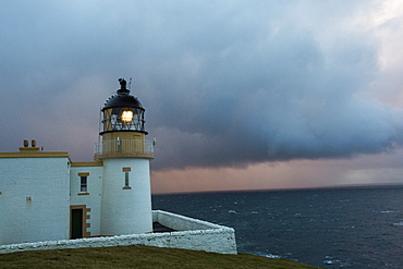 Rain showers at sunset over Stoer Ppoint lighthouse in assynt, north West Highlands, Scotland, UK.