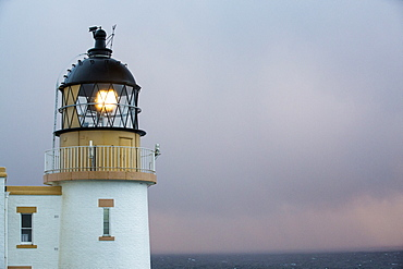 Rain showers at sunset over Stoer Point lighthouse in Assynt, North West Highlands, Scotland, UK.