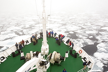 The Russian research vessel, AkademiK Sergey Vavilov an ice strengthened ship on an expedition cruise to Northern Svalbard, with clients on the prow at over 80 degrees north in rotten sea ice, some 550 miles from the North Pole. Latest research shows the Arctic will be ice free in the summer by around 2054.