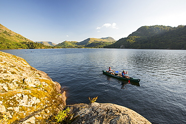 A family paddling in a Canadian Canoe on Ullswater in the Lake District, UK.