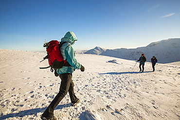Walkers on the Helvellyn Range in winter conditions, Lake District, UK.