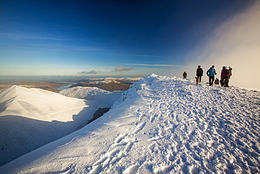 Walkers on Helvellyn summit in winter conditions, Lake District, UK.
