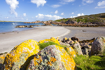 Lichen covered granite boulders at Fionnphort Isle of Mull, Scotland, UK, looking towards Iona.