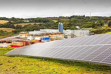 A solar park at Wheal Jane an old abandoned Cornish tin mine near Redruth, UK, that is rediscovering itself as a renewable energy hub, with the old mine buildings in the background.