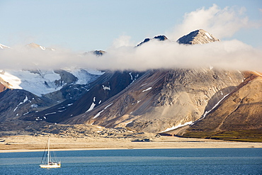 A mountain peak, peeping through the cloud at Bourbonhamna 77¬8 33'Äôn 15¬8 00'Äôe Spitsbergen; Svalbard, with a yacht sailing past.