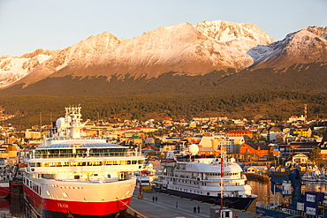 Sunrise over Antarctic expedition ships in the harbour of Ushuaia which is the capital of Tierra del Fuego, in Argentina, it is the most southerly city in the world and the starting point for trips to Antarctica.