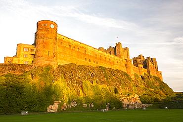 Bamburgh Castle, Northumberland, UK, in glowing light at sunset.