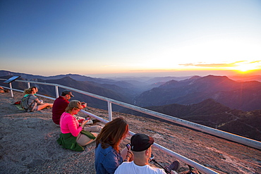 Tourists on the summit of Moro Rock a granite outcrop viewpoint in the Sequoia National Park, Yosemite, USA at sunset.