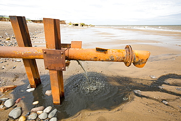 Raw sewage emptying directly onto the beach from a sewage pipe coming from a caravan park in Kilnsea, Spurn Point, Yorkshire, UK.