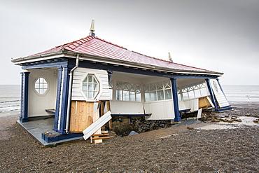 After a week of high tides, storm surges and storm force winds, the sea front promenade of Aberystwyth in Wales has been devastated, with millions of £'s of damage. The crsahing waves punched a large hole in the sea wall and has collapsed Aberystwyth's iconic, Victorian promenade shelter, which has stood for over 100 years. This picture was taken on Wednesday 8th January, 2014, the day the council started to try and clear the thousands of tonnes of beach rubble off the sea front road.