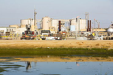A fracking site being fracked near Wasco in California's Central Valley, USA. Fracking for natural gas and oil, has reduced energy prices in the US, but fracking is a water hungry industry, that competes directly with the agricultural sector for water. After a 4 year long drought water is running out.  Fracking also contaminates ground water supplies from all the chemicals that are pumped underground to frack the fossil fuel bearing rocks.
