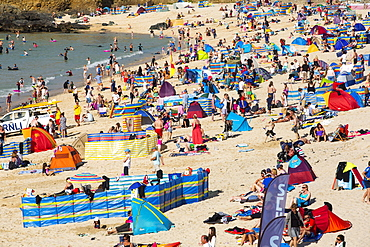 Holiday makers on the beach in St Ives, Cornwall, UK.