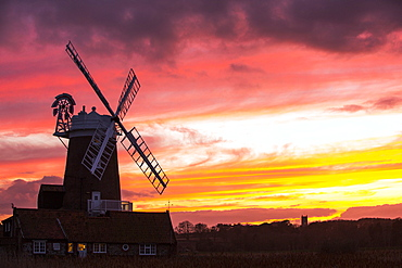 A windmill at Cley Next the Sea, North Norfolk, UK, with Blakeney church in the background at sunset.