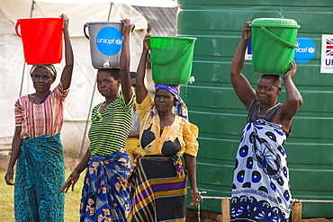 In mid January 2015, a three day period of excessive rain brought unprecedneted floods to the small poor African country of Malawi. It displaced nearly quarter of a million people, devastated 64,000 hectares of alnd, and killed several hundred people. This shot shows a displaced women carrying water in the refugee camp of Chiteskesa refugee camp, near Mulanje.