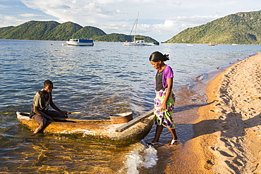 A fisherman in a traditional dug out canoe at Cape Maclear on the shores of Lake Malawi, Malawi, Africa.