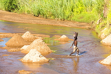 Workers extracting river sands and gravels from a river near Mangochi, Malawi, for use in house building.