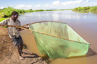 A fisherman catching small fish in the Shire river in Nsanje, Malawi.