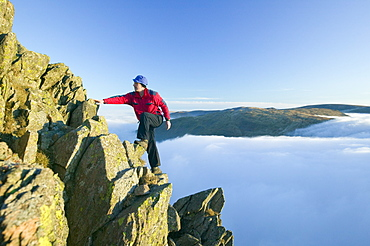 A climber on Red Screes above a temperature inversion in the Lake District National Park, Cumbria, England, United Kingdom, Europe