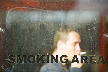A man smoking in a smoking area shelter, United Kingdom, Europe