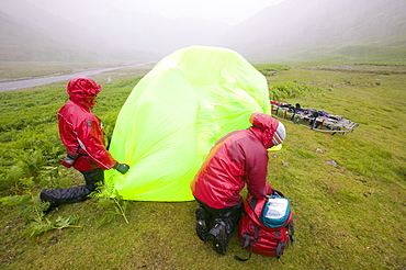 Members of Langdale Ambleside mountain rescue Team treat a collapsed walker suffering from hypothermia protected from the foul weather by a group shelter, Lake District, Cumbria, England, United Kingdom, Europe