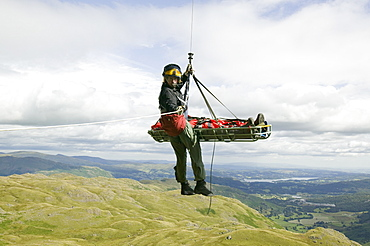 An injured climber with a dislocated shoulder is winched off Jacks Rake, Pavey Ark by the Langdale Ambleside Mountain Rescue Team, Lake District, Cumbria, England, United Kingdom, Europe
