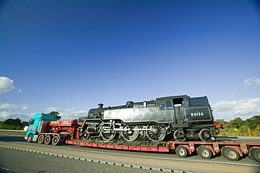 A steam train being transported on a low loader, Leicestershire, England, United Kingdom, Europe