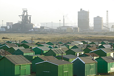 Fishermens huts at South Gare, with the steel plant at Redcar, formerly owned by Corus, now by SSI, Teesside, England, United Kingdom, Europe