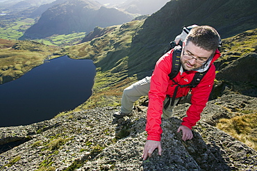 A man scrambling on Pavey Ark in the Lake District, Cumbria, England, United Kingdom, Europe
