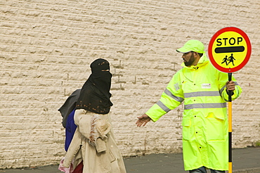 Pakistani women wearing the traditional burkha crossing the road in Burnley with the help of a lollipop man, Lancashire, England, United Kingdom, Europe