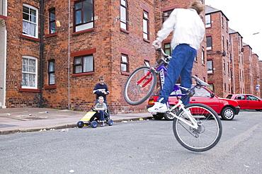 Kids playing around tenement blocks on Barrow Island, Barrow in Furness, Cumbria, England, United Kingdom, Europe
