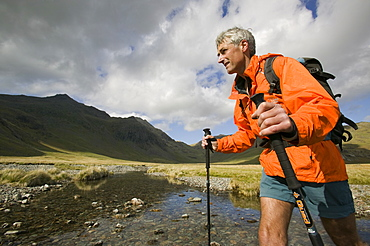 A walker uses trekking poles to help him cross the upper Esk in the Lake District, Cumbria, England, United Kingdom, Europe