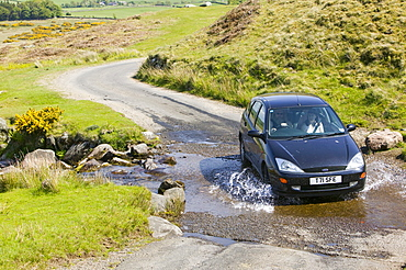 A car crossing a ford in the Lake District near Hesket Newmarket, Cumbria, England, United Kingdom, Europe