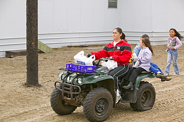 Woman and children on a quad bike on Shishmaref, a tiny island inhabited by around 600 Inuits, between Alaska and Siberia in the Chukchi Sea, United States of America, North America