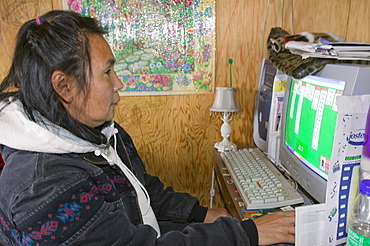 An Inuit woman playing on a computer on Shishmaref, a tiny island inhabited by around 600 Inuits, between Alaska and Siberia in the Chukchi Sea, United States of America, North America