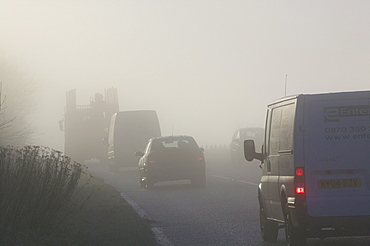 Cars driving in misty conditions on a Lake District road, Cumbria, England, United Kingdom, Europe