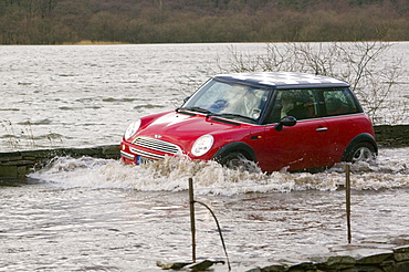Car splashing through flood water in January 2005 when a severe storm hit Cumbria, England, United Kingdom, Europe