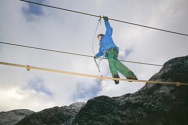 A climber crossing the steal rope bridge in Glen Nevis, Scotland, United Kingdom, Europe