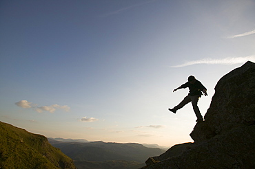 A climber balancing on a crag above Thirlmere in the Lake District, Cumbria, England, United Kingdom, Europe