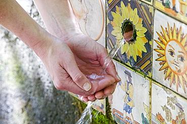 Walker drinks from a mountain spring near Busquistar, Alpujarras, Andalucia, Spain, Europe