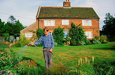 A man watering his garden in Aylsham. Norfolk, England, United Kingdom, Europe