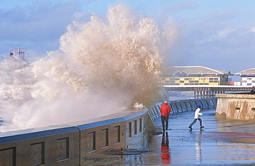 People dodging storm waves breaking over the sea wall at Blackpool, Lancashire, England, United Kingdom, Europe