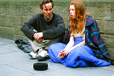 A homeless man and woman sleeping rough and begging on the streets of Leeds, Yorkshire, England, United Kingdom, Europe
