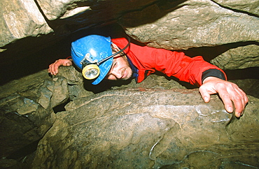 A caver in a tight squeeze in the Yorkshire Dales, England, United Kingdom, Europe
