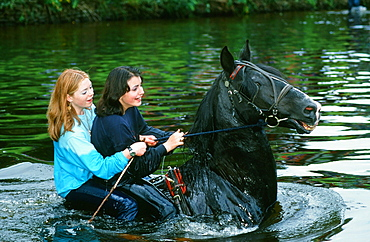 Gypsy girls riding a horse in the River Eden at the Appleby Horse Fair, Cumbria, England, United Kingdom, Europe