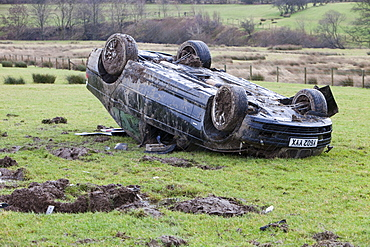 A BMW car crashed on its roof in the middle of a field after leaving the road at high speed on the A66 near Keswick, Cumbria, England, United Kingdom, Europe