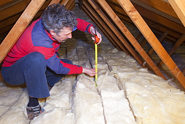 A man measuring the depth of insulation in a house loft or roof space