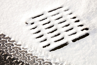 A drain and car print in the snow, England, United Kingdom, Europe