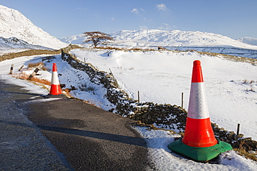 Traffic cones in winter snow on Kirkstone Pass in the Lake District, Cumbria, England, United Kingdom, Europe