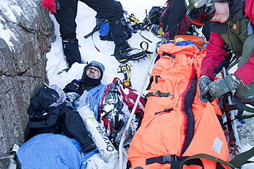 A Navy Sea King helicopter crew and mountain rescue team members treat a seriously injured walker who had fallen 250 , Cumbria, England, United Kingdom, Europe