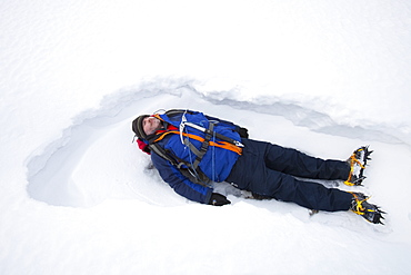 A man lying in the snow on Crinkle Crags in the Lake District, Cumbria, England, United Kingdom, Europe
